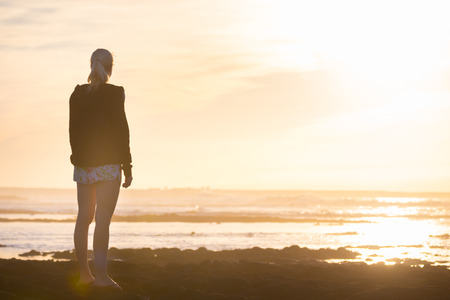casualy: Silhouette of casualy dressed sporty woman watching sunset at the beach. Stock Photo