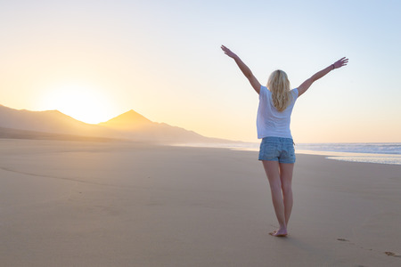 elated: Free woman enjoying freedom feeling happy at beach at sunrise. Serene relaxing woman in pure happiness and elated enjoyment with arms raised outstretched up. Stock Photo