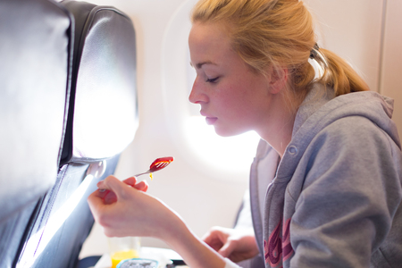 Woman eating meal on commercial airplane.
