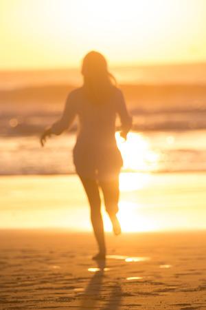 adult footprint: Happy woman enjoying isummer, running joyfully on beach in sunset.