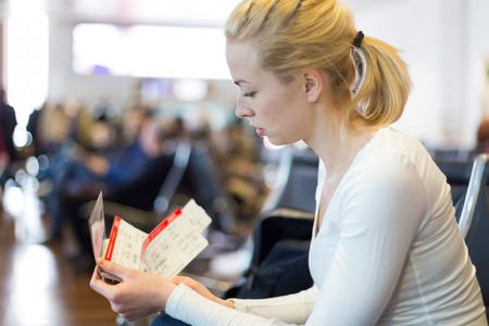 gente aeropuerto: Joven mujer rubia caucsian esperando en las puertas de salida del aeropuerto para embarcar en un avión con billetes en sus manos.