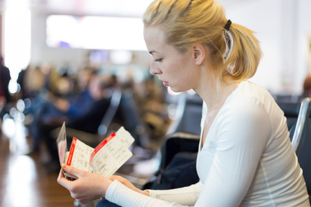 terminal: Young blond caucsian woman waiting on airport departure gates to board a plane with tickets in her hands.