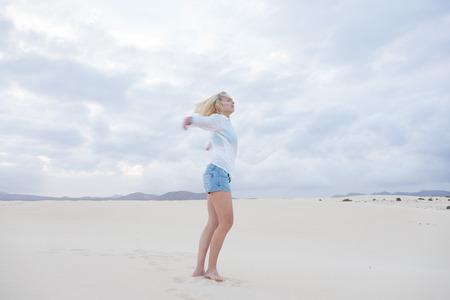elated: Relaxed woman enjoying freedom feeling happy at beach in the morning. Serene relaxing woman in pure happiness and elated enjoyment with arms outstretched.