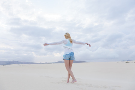 feeling happy: Relaxed woman enjoying freedom feeling happy at beach in the morning. Serene relaxing woman in pure happiness and elated enjoyment with arms outstretched. Copy space. Stock Photo