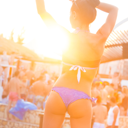 hot sexy girl: Sexy hot girl wearing brazilian bikini dancing on a beach party event in sunset. Crowd dancing and partying at poolside in background. Summer electronic music festival. Hot summer party vibe.