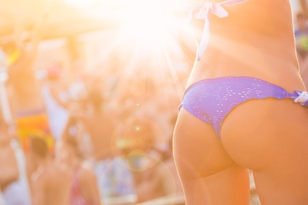 sexy party girl: Sexy hot girl wearing brazilian bikini dancing on a beach party event in sunset. Crowd dancing and partying at poolside in background. Summer electronic music festival. Hot summer party vibe.