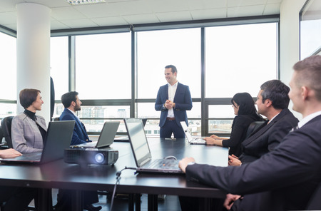 businessman in office: Successful team leader and business owner leading informal in-house business meeting. Businessman working on laptop in foreground. Business and entrepreneurship concept.
