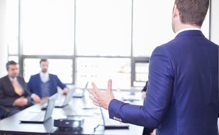 ビジネスマンがオフィスでプレゼンテーションを行ったします。経営者会議や社内ビジネス研修、彼の従業員に事業計画を説明する時に彼の同僚に
