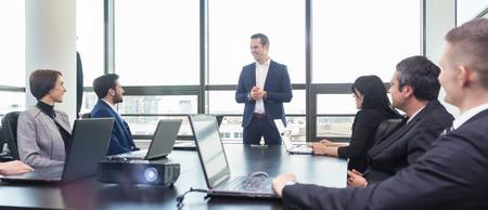 Erfolgreiche Teamleiter und Unternehmer führenden informellen in-house Business-Meeting. Geschäftsmann auf dem Laptop im Vordergrund arbeitet. Unternehmen und Unternehmertum Konzept.