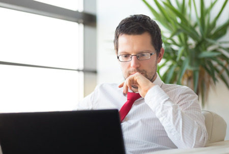 Portrait of successful young businessman in bright modern office focused on work on his laptop computer wearing glasses. Business and entrepreneurship concept. Stock Photo