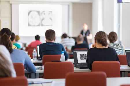 Workshop op de universiteit. Achter mening van studenten zitten en luisteren in collegezaal het doen van praktische taken op hun laptops.