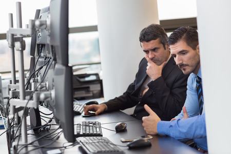 stock traders: Business team working in corporate office. Businessmen trading stocks. Concerned stock traders looking at graphs, indexes and numbers on multiple computer screens. Business crisis and loss concept.