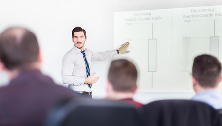 Businessman giving talk on stock trading workshop. Business executive delivering a presentation to his colleagues during meeting or in-house business training.