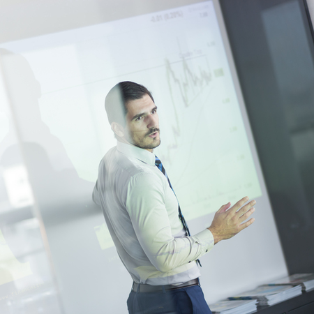 office presentation: Business man making a presentation in front of whiteboard. Business executive delivering a presentation to his colleagues during meeting or in-house business training. View through glass.