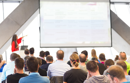 lecture: Woman giving presentation in lecture hall. Female speeker having talk at public event. Participants listening to lecture. Rear view, focus on people in audience. Stock Photo
