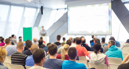 Woman giving presentation in lecture hall. Female speeker having talk at public event. Participants listening to lecture. Rear view, focus on people in audience. Stock Photo