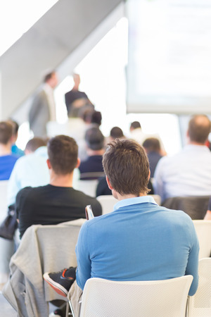 lecture hall: Presentation in lecture hall. Speeker having talk at public event. Participants listening to lecture. Rear view, focus on man in audience. Stock Photo