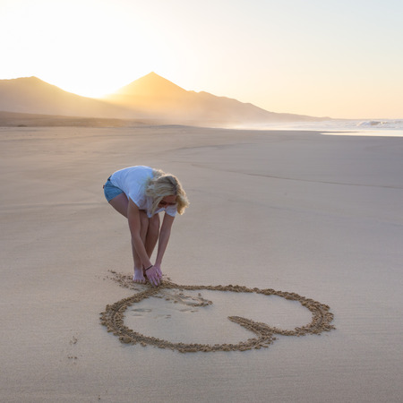 barefooted: Woman drawing heart in sand on beautiful solitary Cofete beach in sunset. Love, travel concept. Fuerteventura, Canary Islands, Spain.