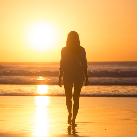 Woman walking on sandy beach in sunset leaving footprints in the sand. Beach, travel, concept. Copy space. Vertical composition. Stock Photo