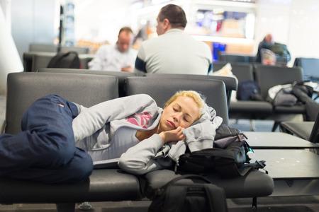 gente durmiendo: viajero femenino cansado que duerme en la jarra de aire puertas de embarque banco con todo su equipaje a su lado. Tireing concepto de viaje. Foto de archivo