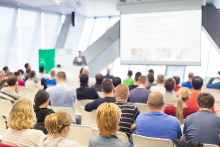 El hombre que da la presentación en el salón de conferencias. speeker macho que tiene charla en acto público. Los participantes escuchan la conferencia. Vista trasera, se centran en las personas en la audiencia.