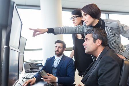 Business team patrząc na danych na wielu ekranach komputerowych w siedzibie firmy. Businesswoman wskazując na ekranie. Ludzie biznesu handel w Internecie. Biznes, przedsiębiorczość i koncepcja pracy zespołowej.