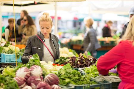 Kobieta kupuje owoce i warzywa na lokalnym rynku spożywczym. Stragan z różnych organicznych warzyw. Zdjęcie Seryjne