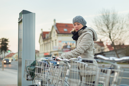 public transport: Lady dialing on keyboard of urban bicycle station. Bikes for rent. Green sustainable ecological public transport. Healthy lifestyle. Stock Photo