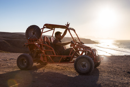 quad: Active man driving quadbike on dirt road by the sea in sunset showing rocking sign to the camera. Stock Photo
