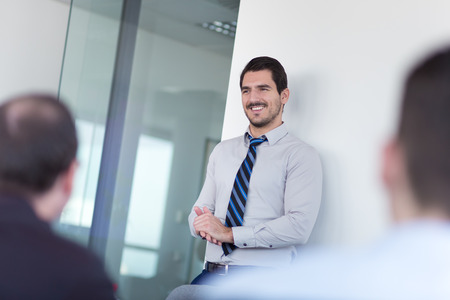 informal: Relaxed cheerful team leader and business owner leading informal in-house business meeting. Business and entrepreneurship concept. Stock Photo