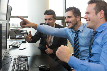 stock traders: Successful business team. Stock traders looking at graphs, indexes and numbers on multiple computer screens. Colleagues in traders office. Business success.