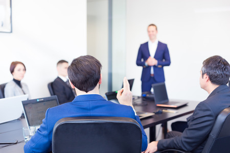 Colleague asking a question to  businessman during a presentation. Successful team leader and business owner  leading informal in-house business meeting. Business and entrepreneurship concept.
