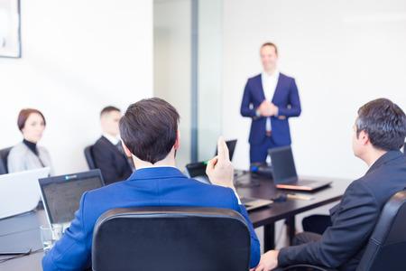 Colega que hace una pregunta al empresario durante una presentación. jefe de equipo exitoso y propietario de la empresa líder en la reunión de negocios en la empresa. Concepto de negocios y el espíritu empresarial. Foto de archivo