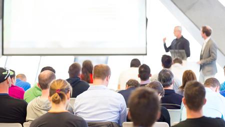 Los hombres que da la presentación en el salón de conferencias. speeker macho que tiene charla en acto público. Los participantes escuchan la conferencia. Vista trasera, se centran en las personas en la audiencia. Foto de archivo