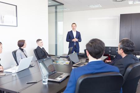 Succesvolle teamleider en ondernemer toonaangevende informele in-house zakelijke bijeenkomst. Zakenman werken op de laptop op de voorgrond. Bedrijfsleven en ondernemerschap concept.