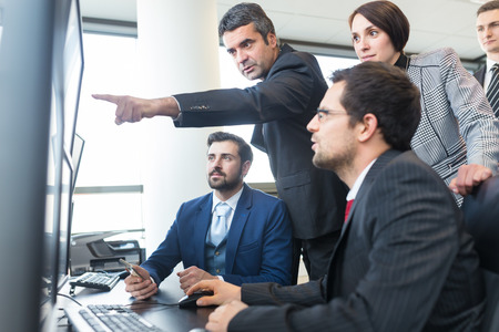work  office: Business team looking at data on multiple computer screens in corporate office. Businessman pointing on screen. Business people trading online. Business, entrepreneurship and team work concept. Stock Photo