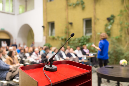 hablante: Female speaker at Business Conference. Audience at the conference hall. Business and Entrepreneurship. Business woman. Focus on microphone. Foto de archivo