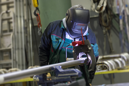 inox: Industrial operator setting  computer controlled process of orbital welding machine in inox pipes manufacturing workshop. Stock Photo