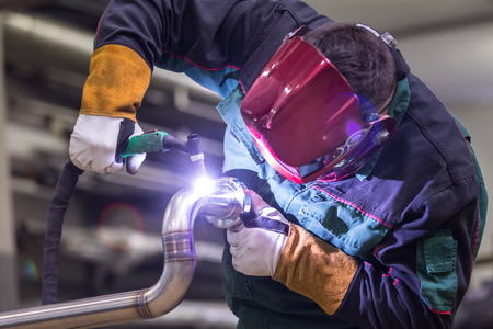 Industrial worker with protective mask welding inox elements in steel structures manufacture workshop. Archivio Fotografico