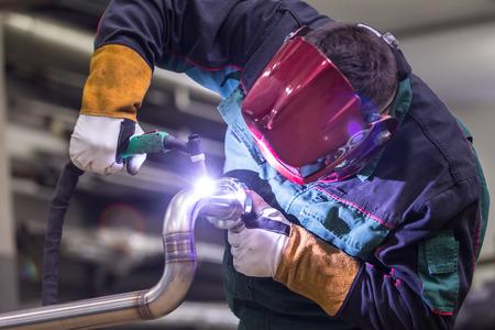 Pracownik przemysłowych z maski ochronne inox spawanie elementów konstrukcji stalowych producenci w warsztatach. Zdjęcie Seryjne