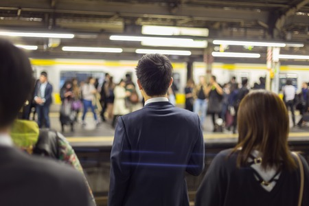 public transport: Passengers traveling by Tokyo metro. Business people commuting to work by public transport in rush hour. Shallow depth of field photo. Stock Photo