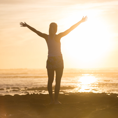 mujer mirando el horizonte: Silhouette of free woman enjoying freedom feeling happy at beach at sunset. Serene relaxing woman in pure happiness and elated enjoyment with arms raised outstretched up.