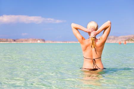 swimm: Young caucasian woman enjoying summer swimm in picture perfect turquoise sea lagoon on Balos beach, Crete, Greece. Stock Photo