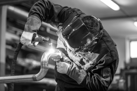 metalwork: Industrial worker with protective mask welding inox elements in steel structures manufacture workshop. Black and white photo.