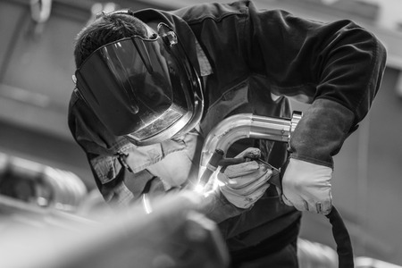 white men: Industrial worker with protective mask welding inox elements in steel structures manufacture workshop. Black and white photo.