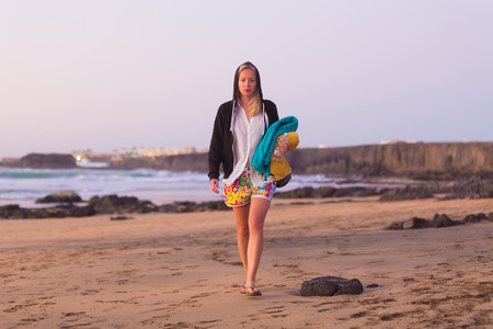 casualy: Casualy dressed active sporty blonde woman walking on sandy surfers Cotillo beach in sunset. Stock Photo