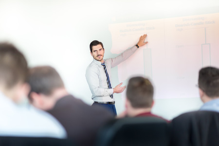 training business: Business man making a presentation at office. Business executive delivering a presentation to his colleagues during meeting or in-house business training, explaining business plans to his employees. Stock Photo