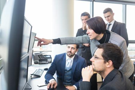 Business team op zoek naar de gegevens op meerdere computerschermen in kantoor. Onderneemster die op het scherm. Mensen uit het bedrijfsleven de handel online. Bedrijfsleven, ondernemerschap en teamwork concept. Stockfoto
