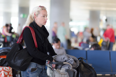 enabling: Casual blond young woman using her cell phone while queuing for flight check-in and baggage drop. Wireless network hotspot enabling people to access internet conection. Public transport.