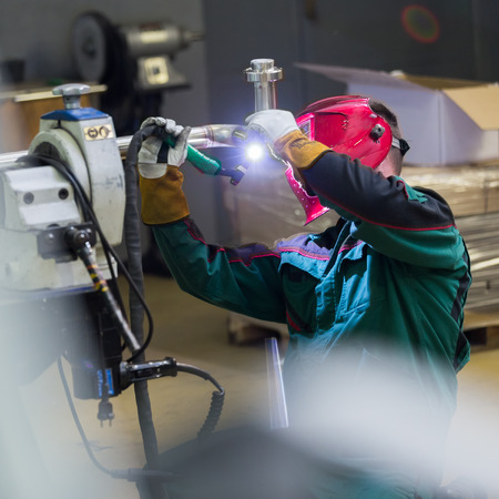 inox: Industrial worker with protective mask welding inox elements in steel structures manufacture workshop. Square composition.